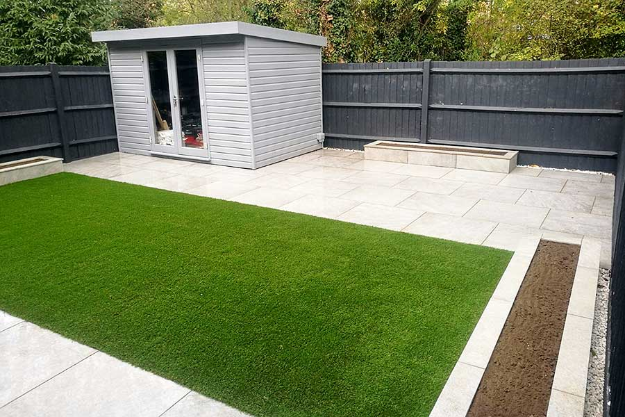 A low maintenance garden with porcelain paving and artificial grass by AWBS Landscaping